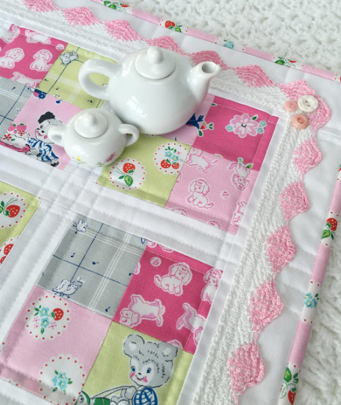 four patch quilt with pink and white crochet trim